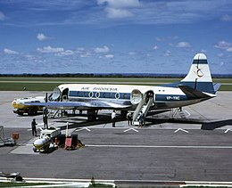 "A white and blue aeroplane on a runway, surrounded by tankers of fuel and other equipment. The tail bears a stylised red Zimbabwe Bird, and the words ""AIR RHODESIA"" are painted above the windows of the cabin. Towards the rear are painted the letters ""YP-YNC"", with the green and white Rhodesian flag rendered above."