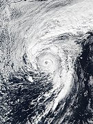 A well-developed hurricane with a defined, clear eye and prominent clouds surrounding it. A large band of clouds also extends north of the main center
