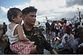 An Armed Forces of the Philippines soldier holds a child as her family waits to be airlifted from Tacloban Air Base Nov. 14, 2013, as part of Operation Damayan 131114-M-FF989-903.jpg