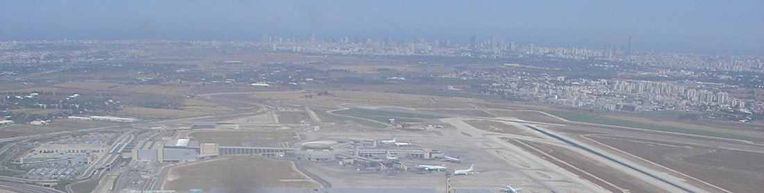 מבט פנורמי מאזור טרמינל 1 לכיוון צפון־מערב: טרמינל 3 (משמאל) ונקודת המפגש של המסלול השקט ושל מסלול הנחיתה הראשי (מימין). מעליה נראים בתי הערים אור יהודה ויהוד, וברקע גורדי השחקים של תל אביב (לצפיה יש להזיז עם העכבר את סרגל הגלילה בתחתית התמונה)