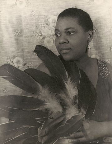 Bessie Smith, an early blues singer, known for her powerful voice Bessie Smith (1936) by Carl Van Vechten.jpg