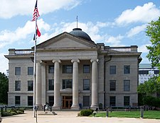 A light-colored three-story stone building with an American flag flying from a pole in front above another red, white and blue striped flag. The building has a pedimented front pavilion with four columns and a small dome at the top from which another American flag is being flown.