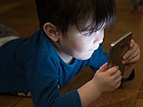 A young boy engaged with a smartphone