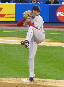 A man in a gray baseball uniform winds up to pitch with his right hand.