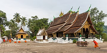 Buddhist monks cleaning the yard at Wat Xieng Thong temple.jpg