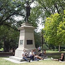 statua di un uomo su una base alta in un parco