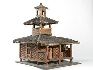Bedug - Model of a Sundanese mosque with bedug hung horizontally in lower right, front part of the building. On the side of the bedug, a slit drum is hung vertically.