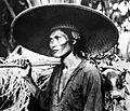 COLLECTIE TROPENMUSEUM Portret van een man met een grote gevlochten hoed en een varken aan zijn draagstok TMnr 10005082.jpg