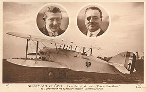 Faded brown postcard with a photograph of a white biplane.  Two oval cameo pictures are above the aircraft, showing the faces of two men.  On the left, is a clean-shaven healthy-looking man in his mid-30s, with a pilot's squint.  On the right, is a slightly more heavyset man with a black eyepatch over his right eye.