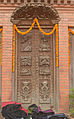 Carved door with Buddha life scenes, Nepal.jpg