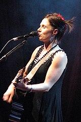 Ela é mostrada na foto de corpo superior e perfil esquerdo.  Ela tem os olhos fechados enquanto ela canta em um microfone e toca sua guitarra.