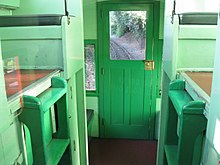 A view of the inside of a caboose with railroad track visible through one of its windows