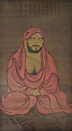 A seated monk in a red robe.