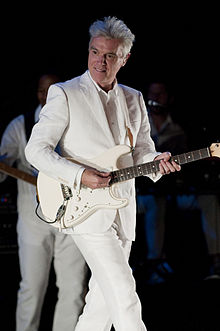 David Byrne looking down at the crowd and smiling while playing guitar