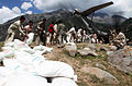 Defense.gov News Photo 100908-F-999K-222 - Local men assist U.S. Marines in offloading hundreds of bags of flour from a KC-130J Super Hercules aircraft at Gilgit Air Base Pakistan on Sept.jpg