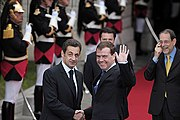 Two men shaking hands, one also waving