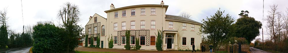 Panorama of a three storey stucco rendered building in a plain Georgian style, with bushes and trees on each side where a boundary wall shelters the gravelled garden from a narrow lane.