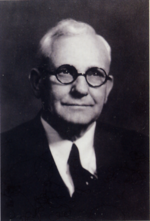 Black and white portrait photograph of an old man wearing glasses.