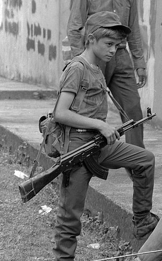 Child abuse - A child soldier in El Salvador, 1990.
