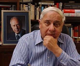 Eitan Haber - Eitan Haber, with a portrait of Yitzhak Rabin behind him.