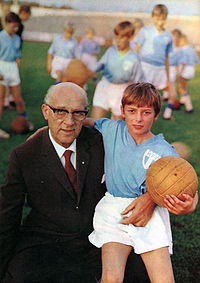 A photograph of an older man with a boy sitting in his lap. The older man, to the left, is bald, wearing glasses and wearing a dark brown business suit with a white shirt and a red tie underneath. The boy is blonde and wears a light blue football shirt and white shorts, with a leather football in his left hand. Several other boys can be seen with similar outfits in the background.