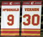 "Two rectangular banners, both white with red and yellow trim at the top and bottom.  The left one says ""1981 – 1989 McDONALD 9"" and the right ""1982 – 2002 VERNON 30"""