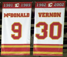 "Two rectangular banners, both white with red and yellow trim at the top and bottom.  The left one says ""1981–1989 McDONALD 9"" and the right ""1982–2002 VERNON 30"""