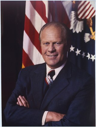 Ford, arms folded, in front of a United States flag and the Presidential seal.