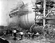 An old photograph showing a large iron paddlewheel ship being launched sideways, with workmen thrusting large baulks of timber under a large drum of iron chains