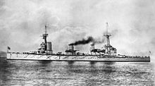 Side view of a large warship with three funnels and two large masts. The ship is stationary, with smoke coming out of the middle and rear funnels.