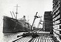 HUA-168946-Afbeelding van het lossen van nog onbehandelde dwarsliggers in de haven bij het houtbereidingsbedrijf (HBI) van de N.S. te Dordrecht. Links het vrachtschip Kamenetz Podolsk.jpg
