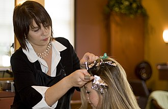 Hair coloring - A hairdresser colors a client's hair.