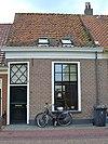Eenvoudig pand onder zadeldak met deur met bovenlicht en vensters met roedenverdeling, achter gevel met nr. 51