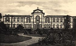 A monochrome photograph showing a path winding through a tropical garden, and leading to a large, two-story neoclassical building with tiled roof, walls in white stucco with dark stone used for quoin blocks, window frames and balustrades
