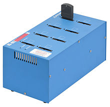 Photo of a burner shown as a blue colored box with eight slots on top, and a cartridge is in one of the slots.