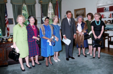 Seven women standing in a row with the President, in the Oval Office, in 1963.