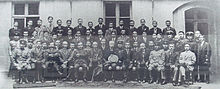 A large group of men sit posed for a photograph.