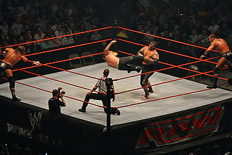 Professional wrestling - A tag team match in progress: Jeff Hardy kicks Umaga, while their respective partners, Triple H and Randy Orton, encourage them and reach for the tags