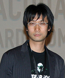 An asian man stands stoically looking at the camera.