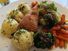 Breaded chicken cutlet served with mashed potatoes, broccoli, carrots, lettuce and garnished with physalis