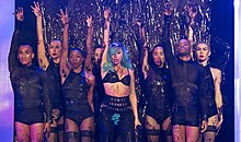 A group of people standing with their right hand raise up. They are decked in black garments with bare legs. Central to them is a woman who has blue hair and tufts of hair from her underarms and at her pubic area.