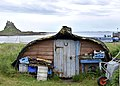Lindisfarne Castle upturned boat used as shed in foreground.jpg