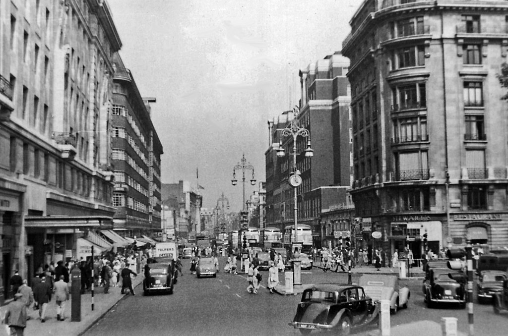 Eastward along Oxford Street outside Marble Arch station, 1955. Bustling as ever, but less road traffic in 1955. To the right is Park Lane, with traffic from Edgware Road and Bayswater Road circling round.