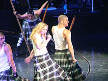 Madonna wearing a white T-shirt and a black-and-white patterned skirt, holding a microphone. She is surrounded by dancers in similar attire, carrying long poles.