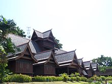 A large intricate wooden house facing right with a forest in the background