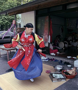 Korean shamanism - A baksu holding a gut.