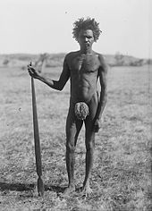 A man standing on flat, grassy ground holding a wooden spear-thrower. He is naked except for a small loin cover.