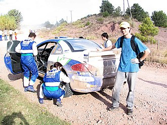 Co-driver - Manfred Stohl and co-driver Ilka Minor changing a tire on a road section of Rally Argentina.