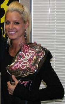 "A blonde Caucasian woman holding a wrestling championship on her left shoulder. She is wearing a black, long-sleeve T-shirt and long silver earrings. The championship belt has a black strap, and the front of the belt is in a pink butterfly design, with the word ""Divas"" in white."