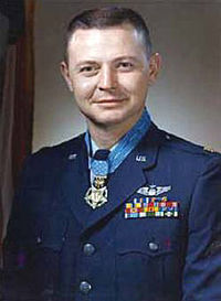 Head and shoulders of a man with short hair and a round face in a dark blue military jacket. Rows of ribbon bars and a winged pin are on his left breast and a medal hangs from a light blue ribbon around his neck.